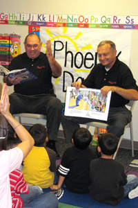 Retired Mesa police chief Dennis Donna, left, and former Paradise Valley police chief John Wintersteen read to children at Phoenix Day, a child develpment center in Phoenix. The center participates in Arizona's First Things First early childhood programs. The officers oppose Proposition 302, the ballot initiative that would terminate funding for the program. (Cronkite News Service Photo by Jennifer A. Johnson)