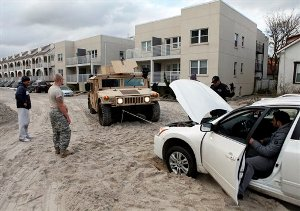 Police and National Guard soldiers help a man free his car from a street covered by over a foot of sand in the aftermath of superstorm Sandy, Tuesday, Oct. 30, 2012, in Long Beach, N.Y. Sandy, the storm that made landfall Monday, caused multiple fatalities, halted mass transit and cut power to more than 6 million homes and businesses.(AP Photo/Jason DeCrow)