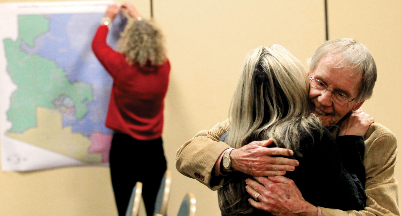 As a staff member takes down the Arizona redistricting map, Arizona Independent Redistricting Commission chair Colleen Mathis gets a hug from Frank Bergen, a Pima County Democrat, at an Arizona redistricting meeting Jan. 17 in Phoenix.
