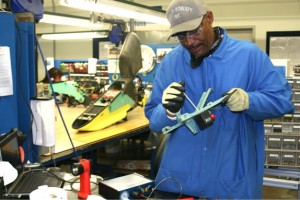 """Ronald Young fashions a pylon used to hold weapons on the AH64D attack helicopter that is built at Boeing's Mesa plant. Mesa Mayor Scott Smith called defense jobs a boon, bringing """"very high-paying jobs"""" to towns like his. (Cronkite News Service photo by Sarah Pringle)"""