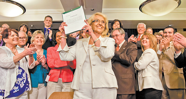 Arizona Gov. Jan Brewer holds up the contentious Medicaid expansion bill after signing it into law. (Photo by Evan Wyloge/Arizona Capitol Times)
