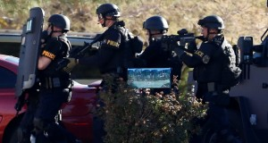 FILE - This Jan. 30, 2013 file photo shows members of the Phoenix Police Department SWAT team preparing to enter the home of a suspected gunman who opened fire at a Phoenix office building, wounding three people, one of them critically, in Phoenix. Phoenix is reviewing five years of data on shootings by police officers in hopes of learning what can be done better and avoiding potential legal trouble. Police Chief Daniel Garcia says the Police Department will study factors and situations that lead to violent confrontations. (AP Photo/Ross D. Franklin, file)