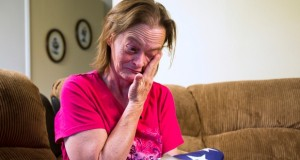 Vicky Olson wipes away a tear May 9, 2014 while talking about her husband, Michael Olson, a Marine veteran who died at home in their garage in March at age 45. Vicky holds their wedding photograph , as well as a United States flag given to her at a memorial service for Michael. (AP Photo/The Arizona Republic, Tom Tingle)