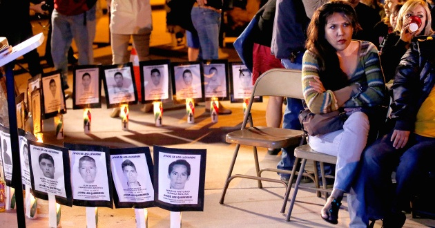 Near a makeshift memorial for immigrants, Christina Felix joins other immigrant rights supporters gathering at the Arizona Capitol to listen to President Barack Obama announce a new program to protect immigrants who reside in the country illegally Thursday, Nov. 20, 2014, in Phoenix. (AP Photo/Ross D. Franklin)