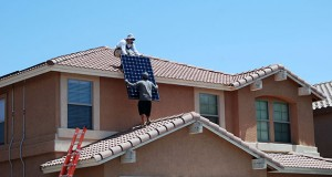 Installers with Sun Harvest Solar hoist solar panels onto a roof in Peoria, Arizona. Installs have slowed a bit for Sun Harvest in the wake of recent fees and proposals to add fees to solar customers. (Photo by Rachel Leingang, Arizona Capitol Times)