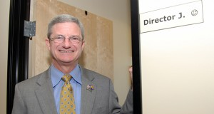 "Department of Economic Security director Tim Jeffries stands outside his office, adorned with a ""Director J :)"" sign. (Photo by Rachel Leingang, Arizona Capitol Times)"