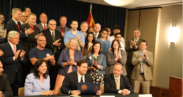 Backed by supporters of Propositions 123 and 124 on May 26, Secretary of State Michele Reagan (L) Gov. Doug Ducey (C) and Supreme Court Justice Clint Bolick (R) certify results of a May 17 special election.