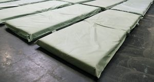 People sleep on thin foam mattresses, placed a few inches apart, on the floor of the overflow shelters on Phoenix's Human Services Campus. (Photo by Gary Grado, Arizona Capitol Times)