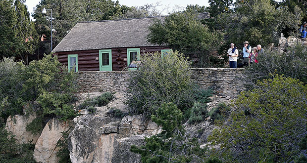 In this Wednesday, May 27, 2015 photo, tourists stand outside a National Park cabin on the south rim of the Grand Canyon, in Ariz. Arizona's rebounding state parks system plans to more than quadruple the number of cabins at parks statewide, one of several projects on the drawing board to improve and expand parks facilities less than a decade after the system struggled to keep parks open as legislators raided funding during the Great Recession. (AP Photo/Matt York)