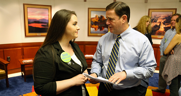 Rachael Pirie's son has severe compromised immune deficiency disorder, which could be included in the state's newborn screening. She talks to Gov. Doug Ducey about her son and shows him photos on February 8, 2017. (Photo by Gary Grado, Arizona Capitol Times)