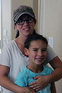 Corinne Bobbie, 37, embraces her daughter Sophia, 8, whose health care costs average $20,000 per year.