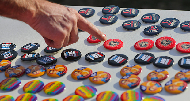 Vendor points to buttons being sold for various causes during the Women's March infront of the White House in Washington, Saturday, Jan. 20, 2018. On the anniversary of President Donald Trump's inauguration, people participating in rallies and marches in the U.S. and around the world Saturday denounced his views on immigration, abortion, LGBT rights, women's rights and more. (AP Photo/Pablo Martinez Monsivais)