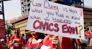 """A woman holds a sign that reads """"Gov. Ducey... is this what you had in mind when you mandated the civics exam?"""". She joined thousands of protesters at Chase Field before marching to the Arizona Capitol on April 26. (Photo by Katie Campbell/Arizona Capitol Times)"""