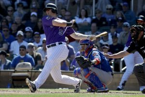 In this March 5, 2018, file photo, Colorado Rockies' DJ LeMahieu bats during a spring baseball game against the Chicago Cubs, in Scottsdale. Major League Baseball is seeking an exemption of baseball players from Arizona's minimum wage law at the Legislature. (AP Photo/Chris Carlson, File)