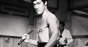 Martial-arts star Bruce Lee holds nunchucks in a scene from one of his movies.