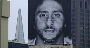 In this Sept. 5, 2018, file photo, a large billboard stands on top of a Nike store showing former San Francisco 49ers quarterback Colin Kaepernick, at Union Square in San Francisco. Nike is pulling a flag-themed tennis shoe after Kaepernick complained to the shoemaker, according to the Wall Street Journal. (AP Photo/Eric Risberg, File)