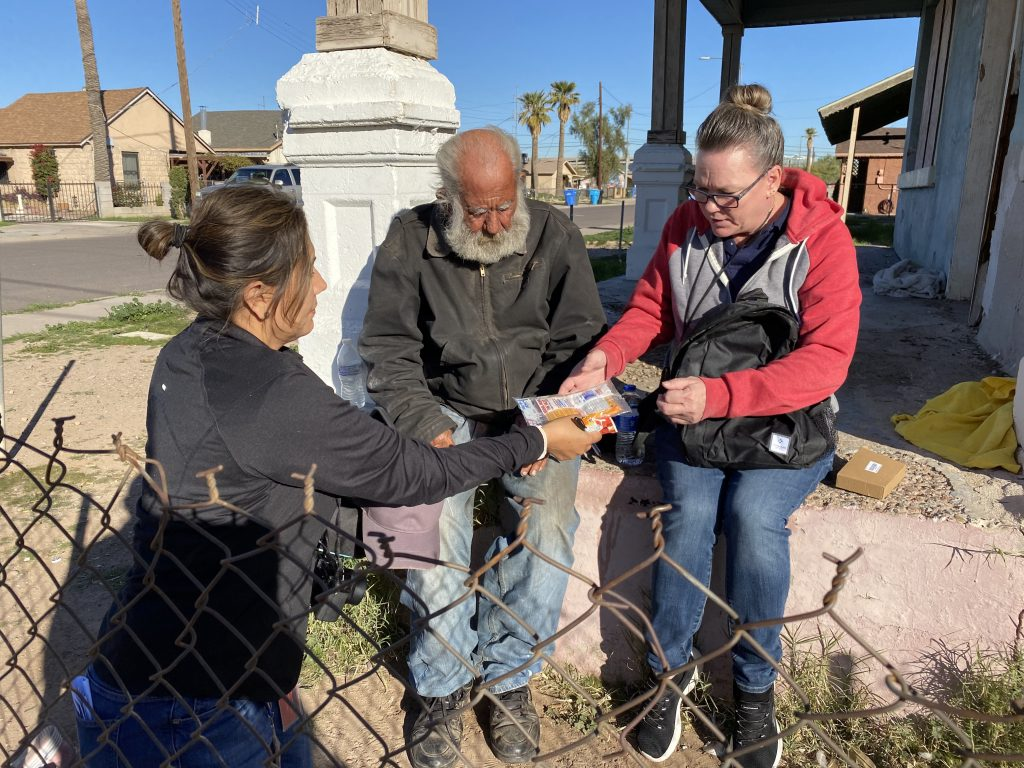 Maria Pina of Maricopa Association of Governments , left, and Tara Devlin of Community Bridges Inc. , far right, give hand warmers to Tony Cortes, who has been homeless for more than 4 years. (Photo by J.J. Santos/Cronkite News)