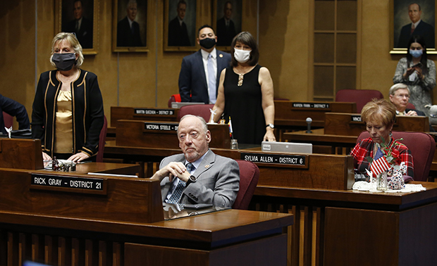 State Sen. Kate Brophy McGee, left, R-Phoenix, stands with Sens. Martin Quezada, back middle, D-Phoenix, and Victoria Steele, second from right, D-Tucson, as they vote to adjourn the Arizona Senate legislative session as Majority Leader Rick Gray, front left, R-Sun City, and Sen. Sylvia Allen, front right, R-Snowflake, stay seated Tuesday, May 26, 2020, in Phoenix. The Arizona Senate's plan to pass a series of House bills and possibility consider two pieces of coronavirus-related legislation were upended Tuesday when a majority of members quickly voted to adjourn for the year in a 16-14 vote, with three Republicans joining the Democrats for the majority. (AP Photo/Ross D. Franklin)