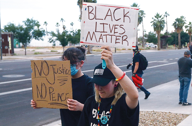 People march near Phoenix Police Headquarters, Saturday, May 30, 2020, in Phoenix, while protesting the death of George Floyd, a handcuffed black man who died in Minneapolis police custody on May 25. (AP Photo/Ross D. Franklin)
