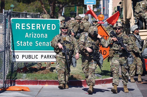 Arizona National Guardsmen disembark from military vehicles near the Arizona Capitol on Tuesday, June 2, 2020, in Phoenix, where there have been several days of protests over the death of George Floyd, who died May 25 after being restrained by Minneapolis police. (AP Photo/Ross D. Franklin)