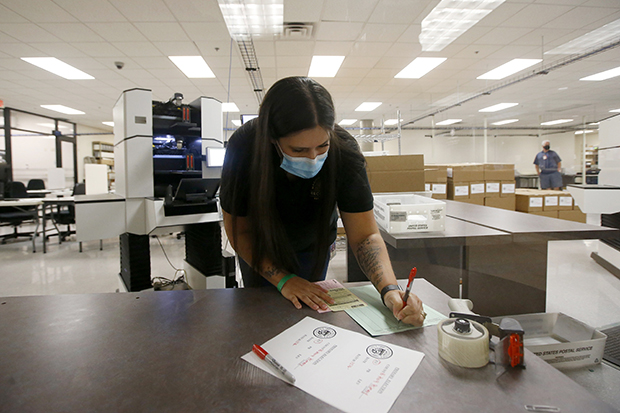 An official with the Maricopa County Recorder's Office fills out paperwork after ballots were counted for the primary election Tuesday, Aug. 4, 2020, in Phoenix. (AP Photo/Ross D. Franklin)