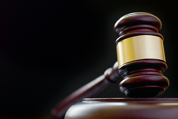 Wooden judges gavel with a shiny brass band resting upright on a wooden base, close up low angle view with focus to the head of the gavel on a dark background with copyspace
