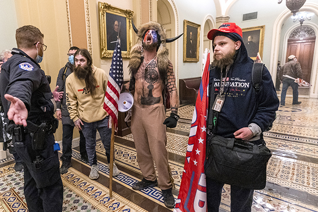 "In this Wednesday, Jan. 6, 2021 file photo, supporters of President Donald Trump, including Jacob Chansley, center with fur hat, are confronted by Capitol Police officers outside the Senate Chamber inside the Capitol in Washington. Chansley's lawyer says that he reached out White House Chief of Staff Mark Meadows about a possible pardon on behalf of the Arizona man, acknowledging it might be a reach but that ""there's nothing to lose."" (AP Photo/Manuel Balce Ceneta)"