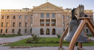 An old watchtower bell is mounted on the sidewalk in front of the state capitol building in Phoenix AZ
