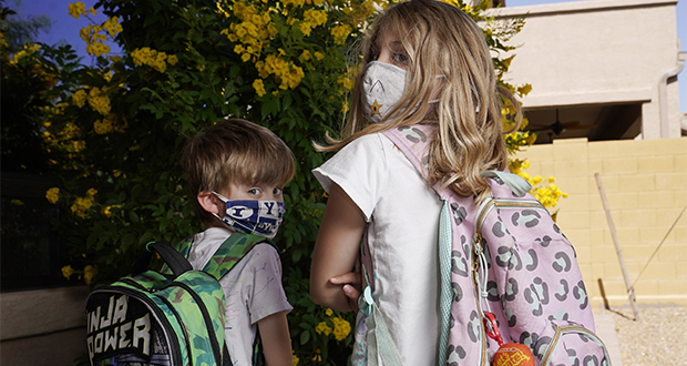 Angela Black, right, with her brother Luke Black at their home, pose for a photo Tuesday, May 11, 2021, in Mesa, Ariz. The students, a third grader and kindergartner, attend a school where mask wearing is optional. (AP Photo/Ross D. Franklin)