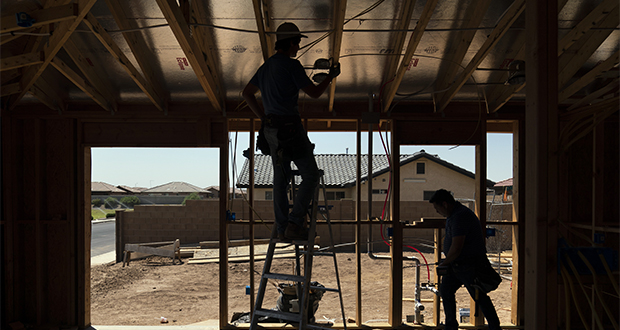Electricians install wires at a newly constructed home Thursday, Aug. 19, 2021, in Somerton, Ariz. The overwhelmingly Hispanic community has grown enough over the last decade that it's also building a new elementary school. But the Census Bureau says Somerton actually lost 90 residents during the that time, putting its official population at 14,197 people, not the 20,000 that the mayor expected. (AP Photo/Jae C. Hong)